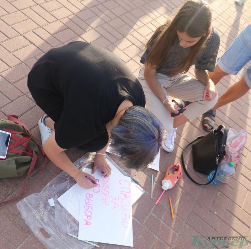 Девушки создают плакат во время протестной акции