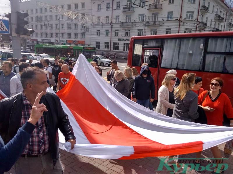 люди несут огромный бело-красно-белый флаг